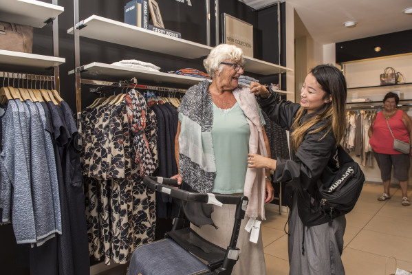 Woman looking for new clothes while walking with her Rollz Flex rollator