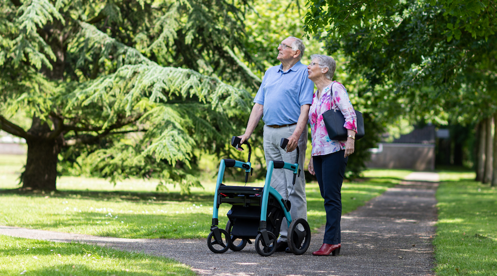 Man with rollator walking in the park with his wife