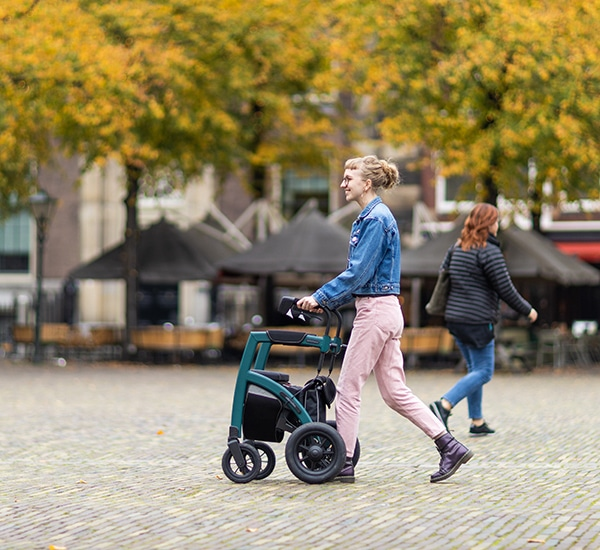 Blond girl walking with a modern rollator in a city center