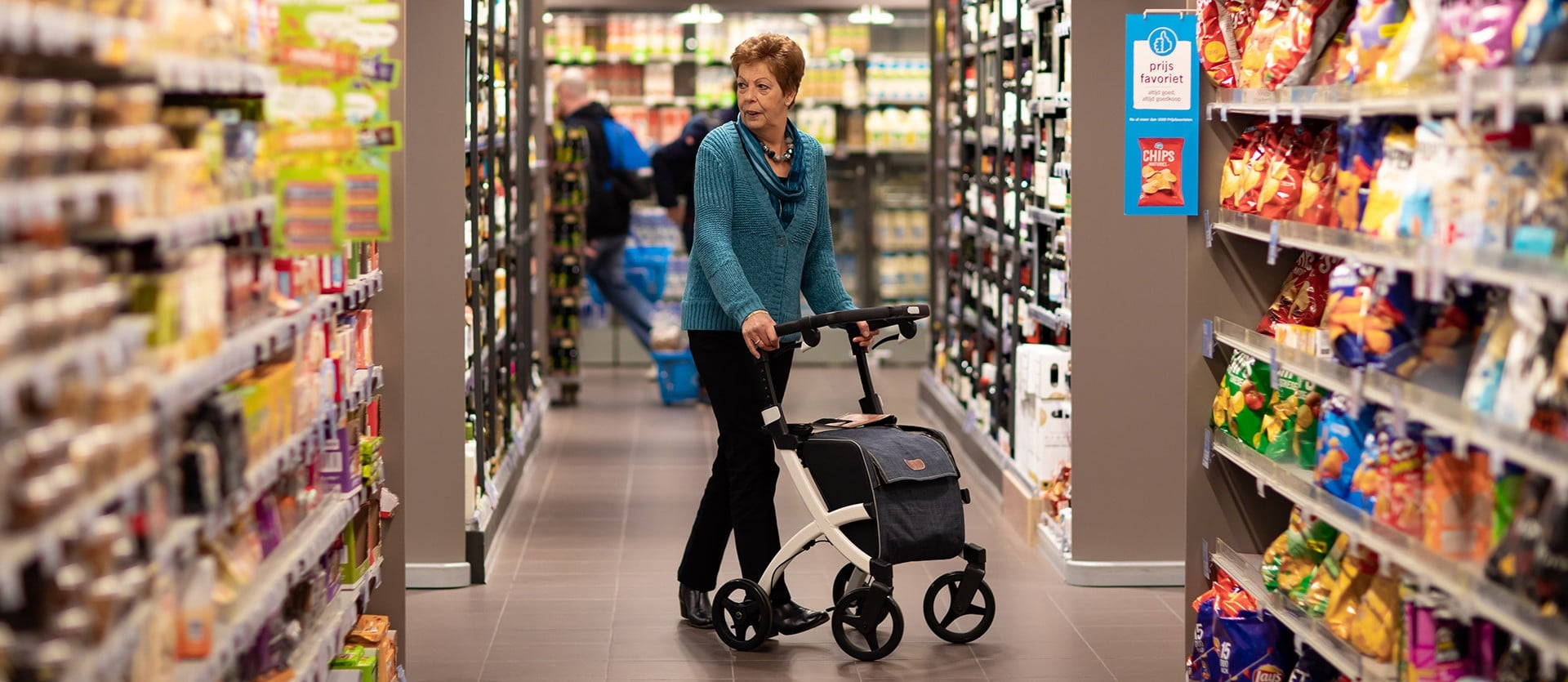 Woman walking with a Rollz Flex rollator with big bag in a supermarket