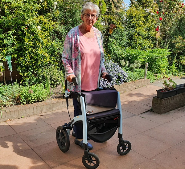 Woman using a walker that was transformed into a Parkinson rollator