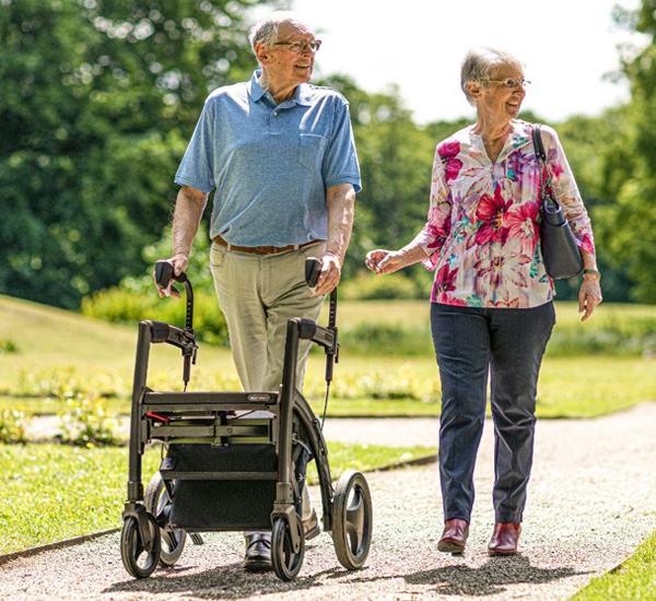 Mann mit Mobilitätsproblemen geht unterstützt