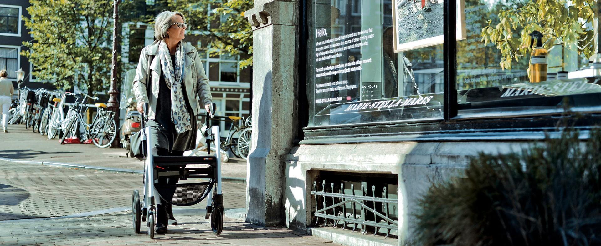 Dame loopt met een rollator in Amsterdam en kijkt naar een etalage.